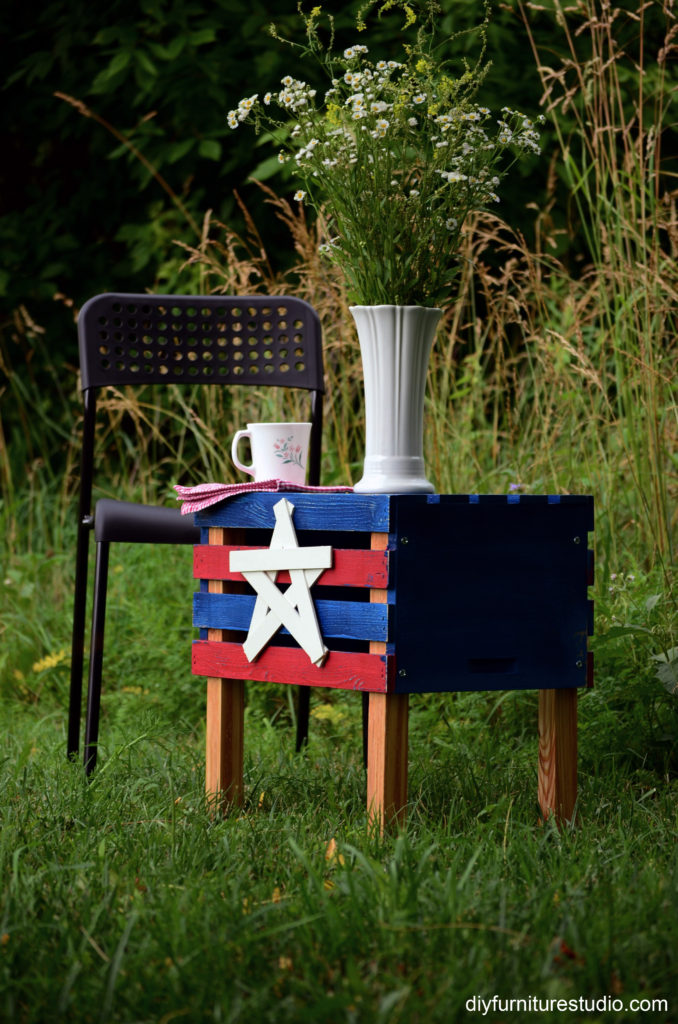 DIY patriotic red, white, and blue side table made with a crate turned upside down and wood legs.