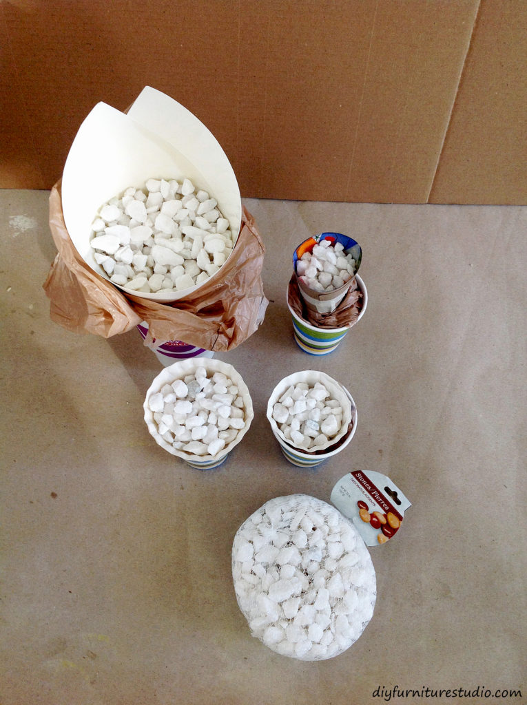 Molds for cement cone Christmas trees filled with white stones.
